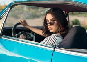 Woman in car with sunglasses